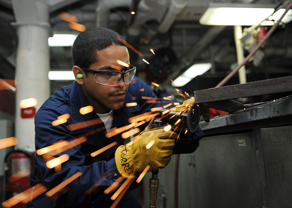 1024px-US_Navy_101006-N-6427M-078_Hull_Maintenance_Technician_Fireman_Ruben_Torres_of_Bloomington,_Ind.,_grinds_down_excess_welds_during_the_fabrication_o